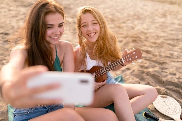 Friends enjoying playing ukulele taking selfie at beach