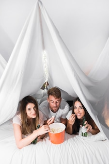 Friends enjoying the popcorns and drinks lying on bed