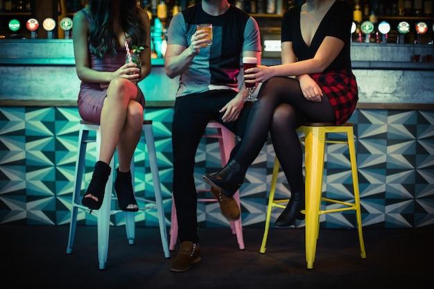 Друзья наслаждаются напитками за стойкой
