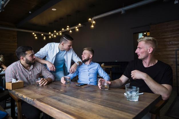 Друзья наслаждаются напитками в баре