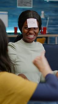 소파에서 휴식을 취하는 동안 함께 시간을 즐기는 친구들이 이마에 붙은 스티커 메모를 사용하여 게임을 추측합니다.