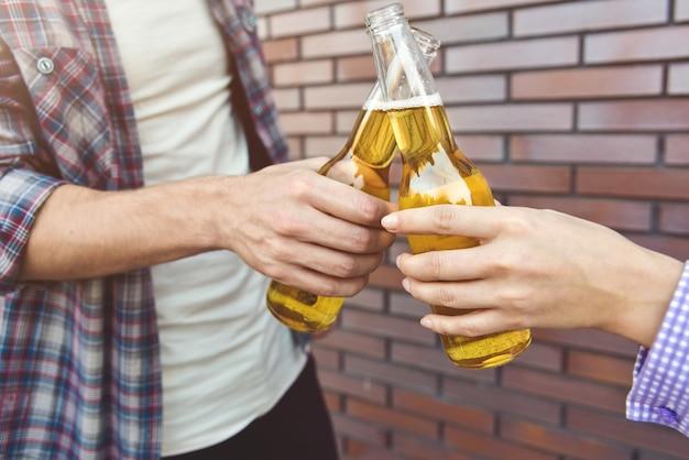 갈색 벽돌 벽에 맥주와 함께 즐기는 친구
