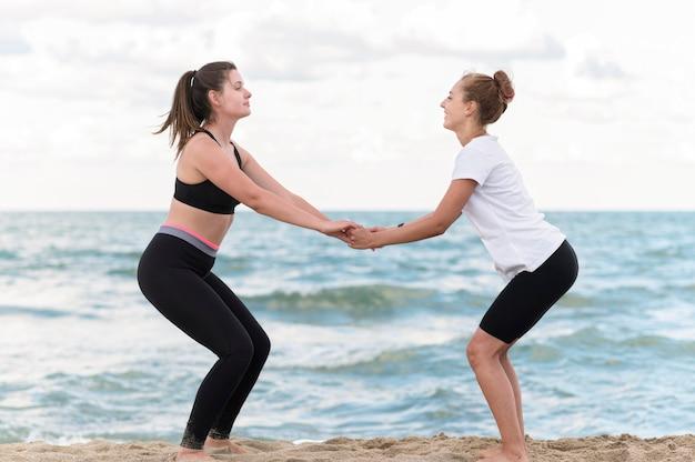 ビーチサイドビューで運動する友達