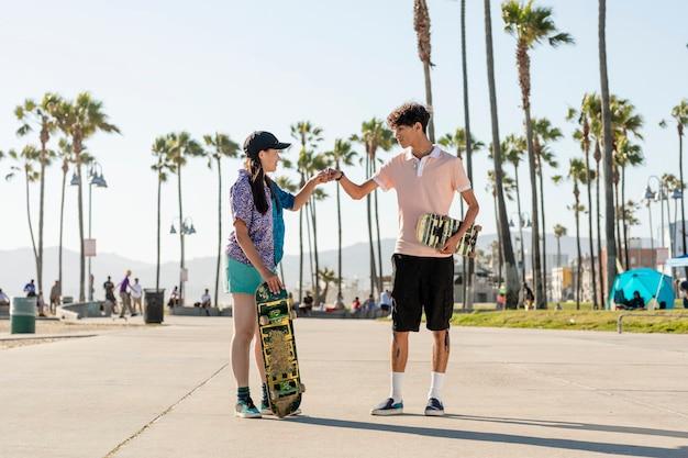 友達のフィストバンプ、ロサンゼルスのベニスビーチでスケーター