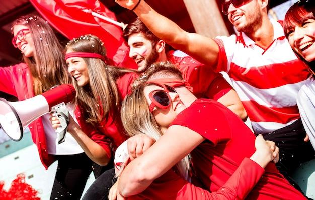 スタジアムでサッカーの試合イベントを見てお互いを抱きしめている友人のサッカーサポーターファン-スポーツ世界選手権のコンセプトのゴール後に興奮して楽しんでいる赤いtシャツで若い人々のグループ