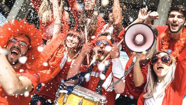 Друзья футбольных болельщиков смотрят футбольный матч на стадионе - наклонная композиция