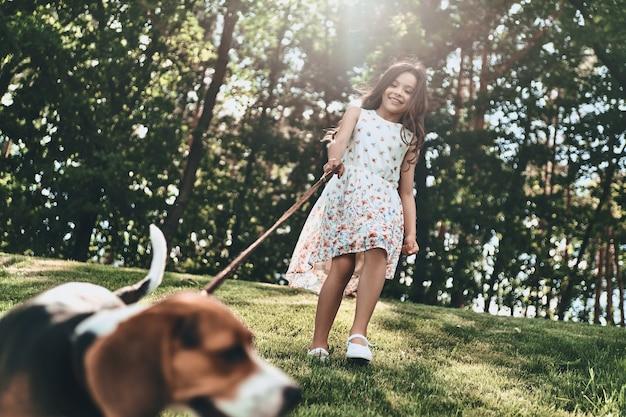 永遠の友達。屋外を歩きながら犬と遊ぶかわいい女の子の全長