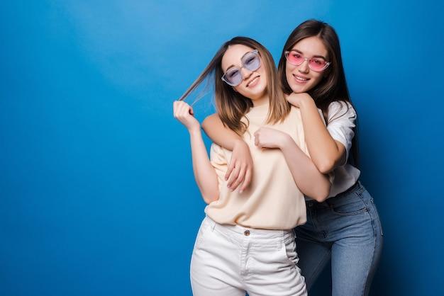 영원히 친구. 파란색 벽에 미소로 포즈를 취하는 선글라스에 두 귀여운 사랑스러운 여자 친구