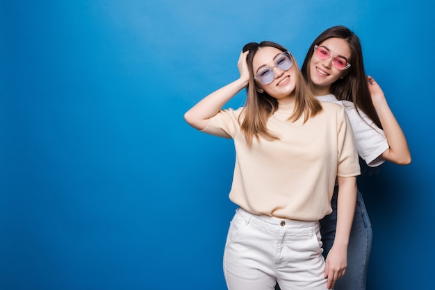 Friends forever. two cute lovely girl friends in sunglasses posing with smile on blue wall