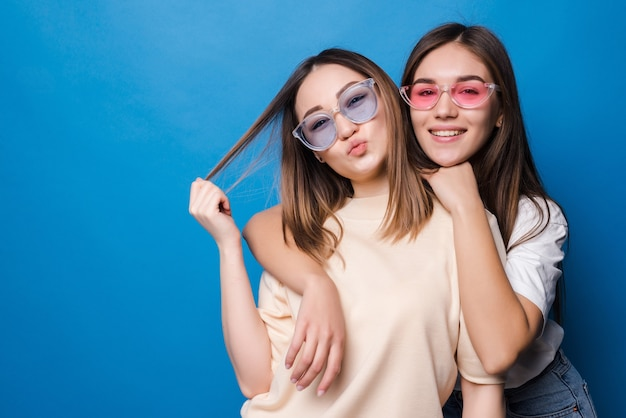 Friends forever. two cute lovely girl friends in sunglasses posing with smile isolated on blue wall