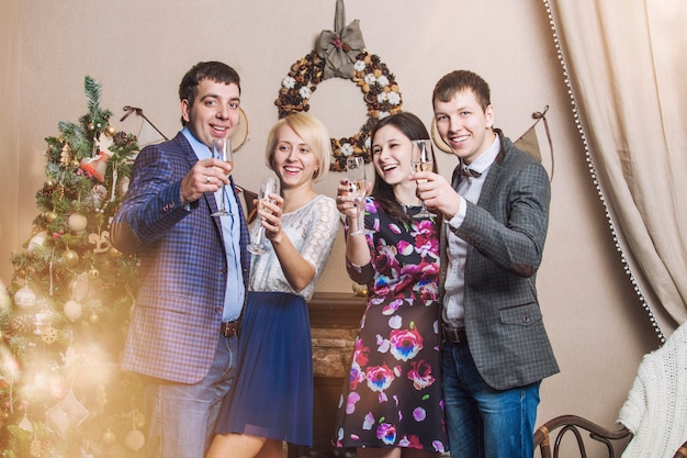 Friends of four men and women with bacale celebrate with champagne in the christmas interior