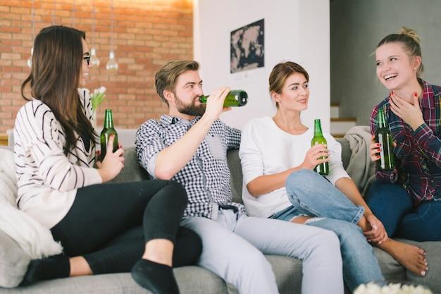屋内に集まる友達。ビールを飲む。