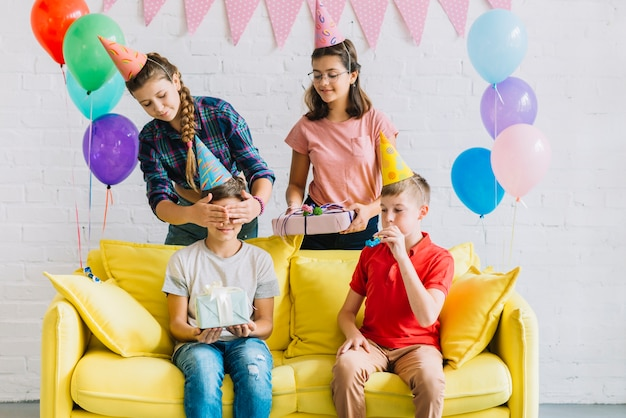 Friends giving surprise gift to boy sitting on sofa
