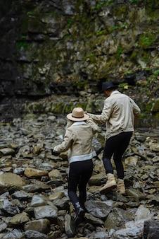 Друзья идут по каменистой дороге. женщина и мужчина гуляют по парку. пара путешествует по красивым местам. туристы идут по горной дороге.