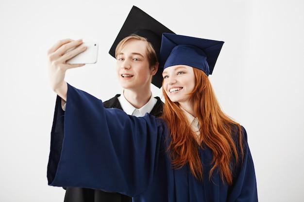 Laureati degli amici dell'istituto universitario in cappucci che sorridono facendo selfie.