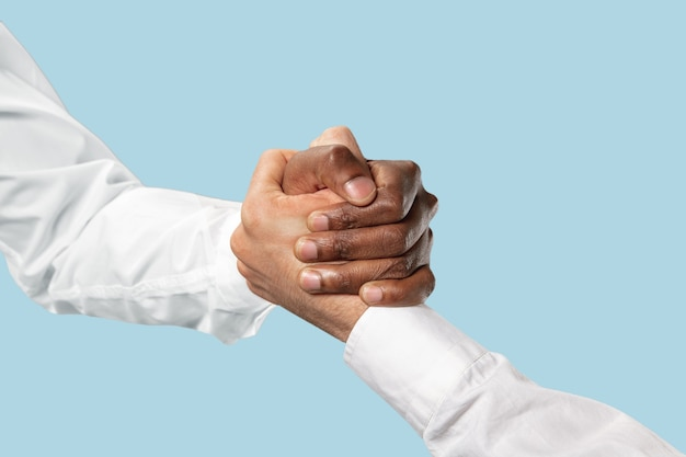 Friends greetings sign or disagreement. two male hands competion in arm wrestling isolated on blue studio background. concept of standoff, support, friendship, business, community, strained relations.