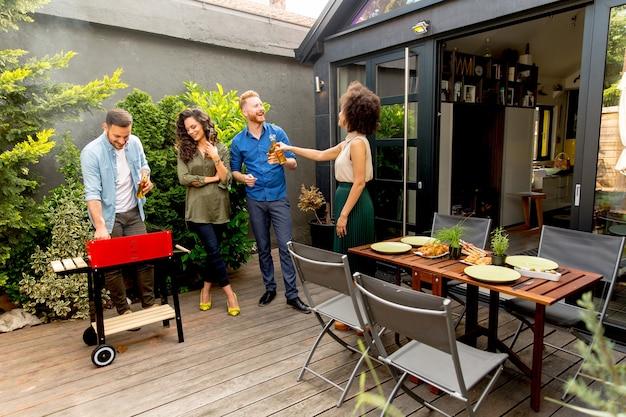屋外でバーベキューパーティーを楽しんで食べ物を食べる友人