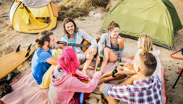 Friends group having fun together at beach camping party - happy friendship travel concept with young people travalers playing guitar and drinking bottled beer at summer surf camp