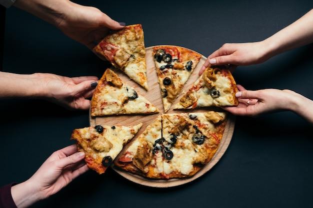 Группа друзей людей, принимающих кусочки пиццы