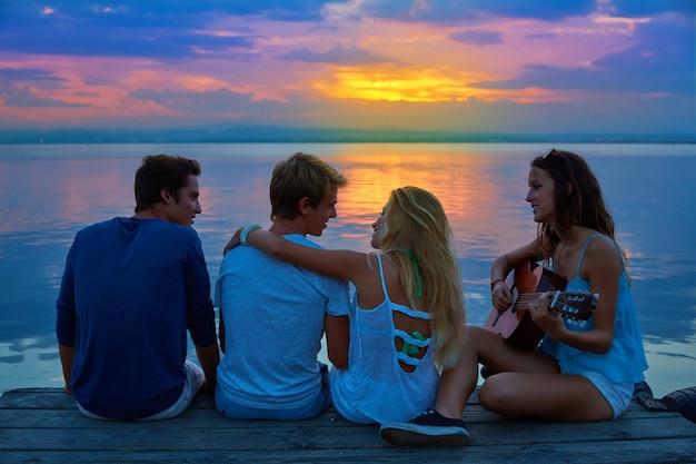 夕暮れ時に日没の桟橋でギターを弾く友人グループ