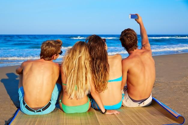 Friends group selfie photo sitting in beach sand