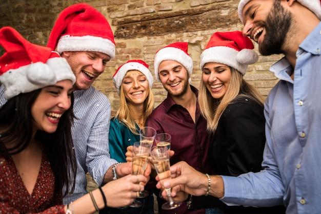 Группа друзей в шляпах санта-клауса празднует рождество