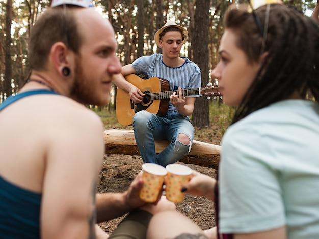 친구 기타 음악 커플 피크닉 파티 자연 개념입니다. 여행자의 라이프 스타일. 하이킹의 행복한 순간.