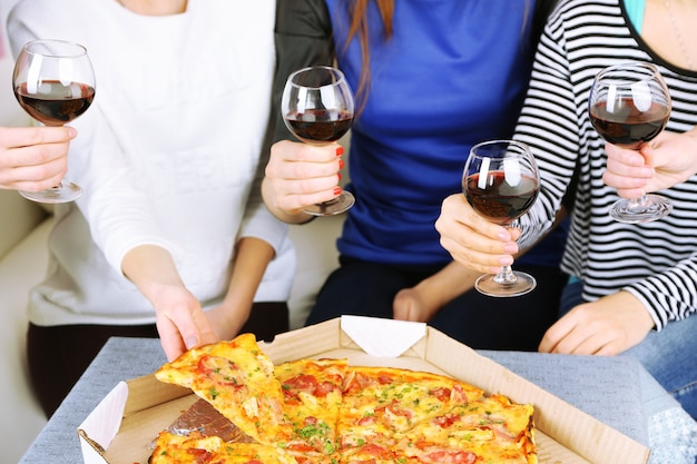 Friends hands with glasses of wine and pizza, close up