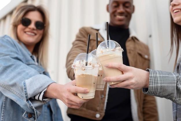 Amici che vanno in giro gustando una tazza di caffè
