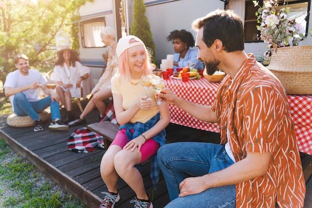 친구들은 화창한 날에 캠핑카와 함께 피크닉을 합니다.