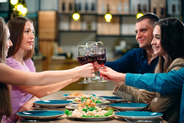 友達はレストランで楽しんでワインを飲む