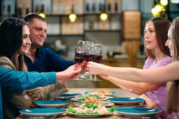 친구들은 레스토랑에서 즐거운 시간을 보내고 와인을 마 십니다.