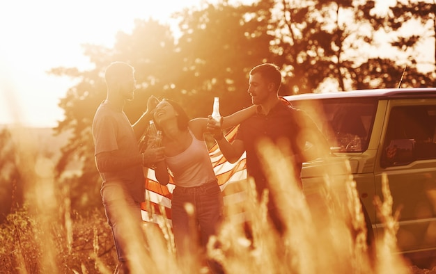 친구는 미국 국기와 함께 그들의 녹색 차 근처 야외에서 좋은 주말을 보냅니다.