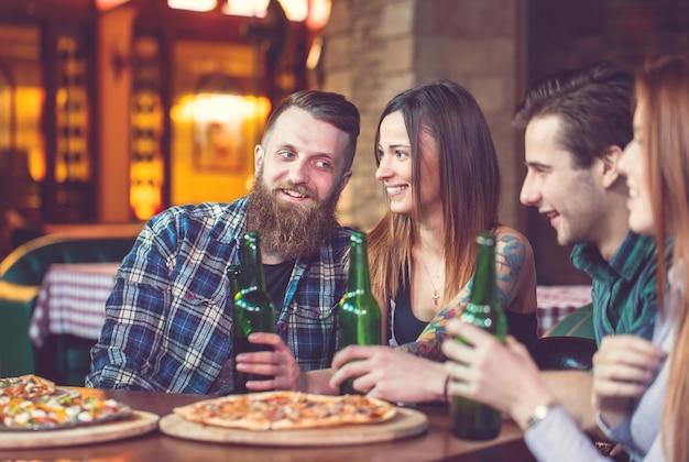 バーでドリンクを飲んでいる友人、彼らはビールとピザと木製のテーブルに座っています。