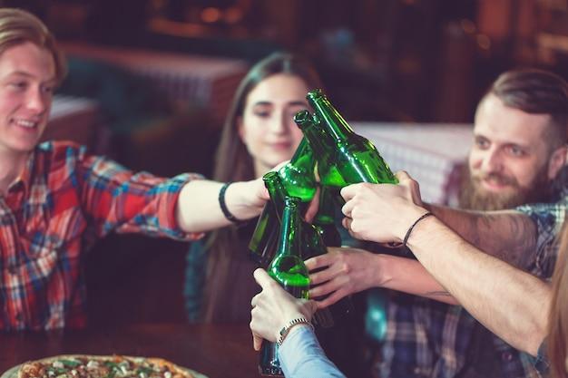 友達がバーでドリンクを飲みながら、彼らはビールとピザと木製のテーブルに座っています。