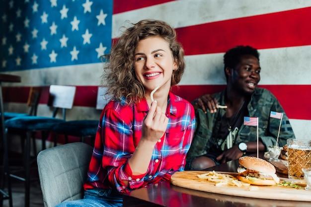 Друзья отдыхают в баре вместе, женщины и мужчина в кафе, разговаривают, смеются, едят фаст-фуд.