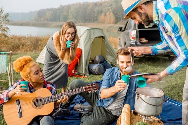 キャンプでのピクニック中に大釜で調理されたスープでおいしい夕食を食べている友人