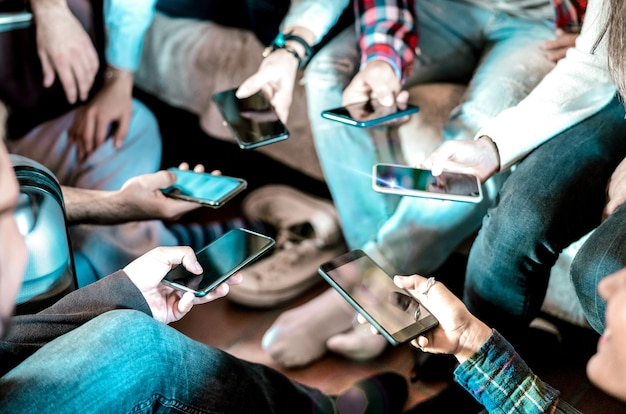 Друзья увлекаются с помощью мобильного смартфона дома