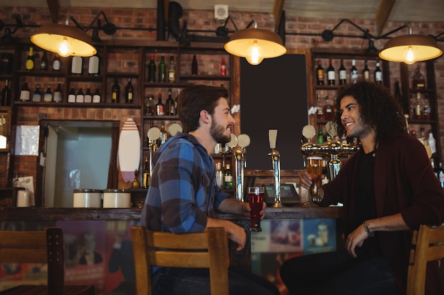 Друзья пьют пиво за барной стойкой