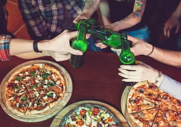 Friends having a drinks in a bar, they are sitting at a wooden table with beers and pizza.