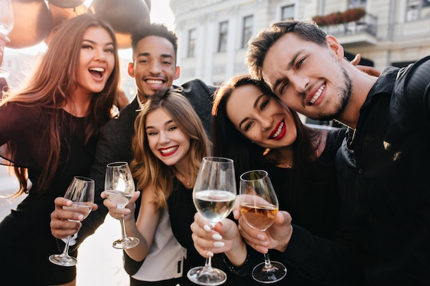 Друзья веселятся и пьют шампанское на открытом воздухе