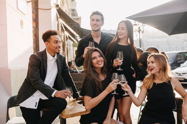 屋外でシャンパンを楽しんで飲んでいる友達