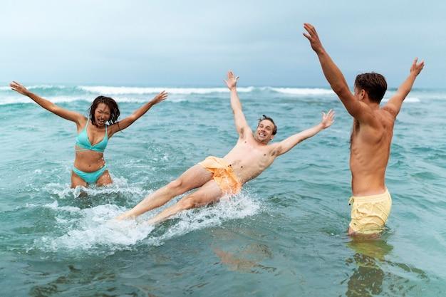 해변 미디엄 샷에서 즐거운 시간을 보내는 친구들