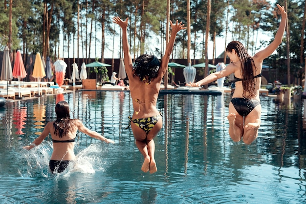 Friends having fun by jumping from poolside into water.