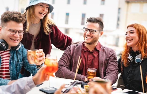 Друзья веселятся, пьют в баре под открытым небом после работы