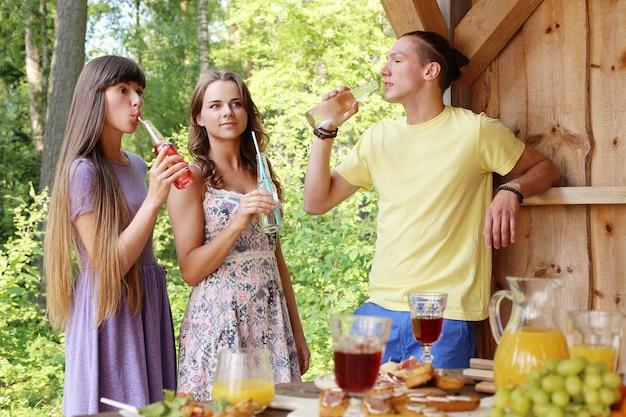 Amici che si divertono e bevono nel campo