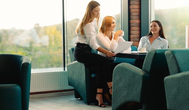 新しいプロジェクトの下でブレーンストーミングをしている現代のオフィスでコーヒーを飲むのを楽しんでいる友人。若い女性は、コーヒーブレイクで時間を過ごしてテーブルに一緒に座っていることについて話し合います。