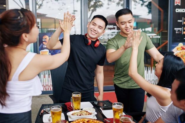 Друзья веселятся во время встречи в кафе