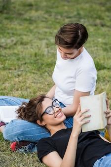 Друзья веселятся в парке чтения книг