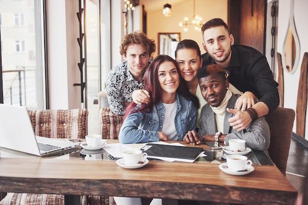 Amici che si divertono al ristorante. tre ragazzi e due ragazze che fanno selfie e ridono.